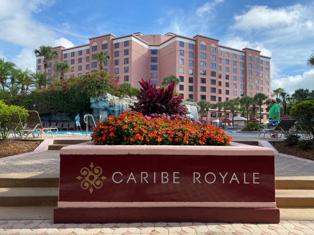 """A sign with the words """"Caribe Royale"""" is in the foreground with red impatien flowers just before two steps that lead up to a pool deck. The pool with a waterful is in the middle ground and the hotel building is soft pink in the background beneath blue skits."""